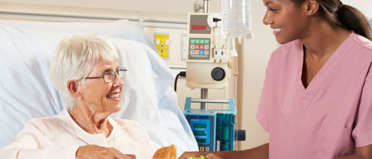 Patient âgé mangeant son repas à l'hôpital servi par une aide soignante